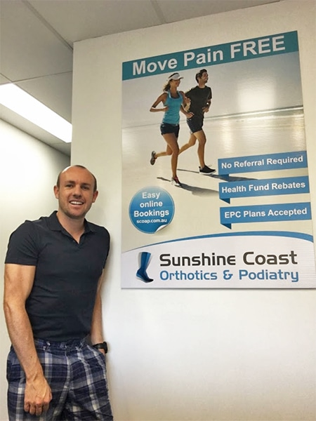 Director of Sunshine Coast Orthotics & Podiatry, Dean Taylor posing for photo next to sign | Podiatrist Sunshine Coast